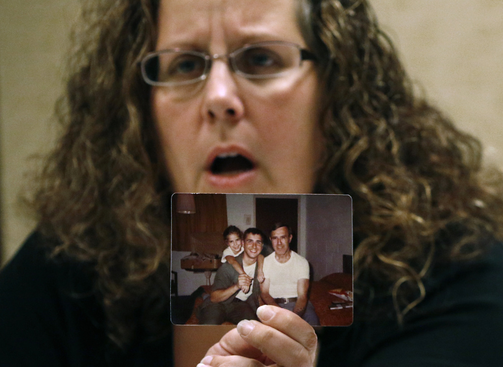 Alexa MacPherson, a victim of clergy sex abuse, holds a photograph of herself as a child as she reacts, Wednesday, Dec. 20, 2017, in Boston, to the death of Cardinal Bernard Law, the disgraced Boston archbishop who epitomized the Catholic Church's failure to protect children from sexually abusive priests. Law died Wednesday in Rome at age 86.  (AP Photo/Bill Sikes)