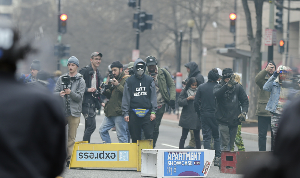 Protesters face off with police in downtown Washington on Inauguration Day. The first six people put on trial for violence at the protest were acquitted Thursday. Prosecutors told jurors there was no evidence the six were personally involved in the violence but argued that they chose to remain with the group, providing cover for the culprits. Left, the six included Brittne Lawson, center, Alexei Wood, left, and Oliver Harris.