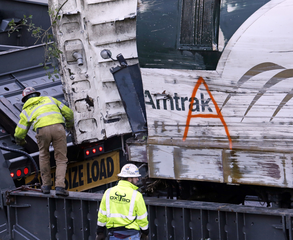 The engine from an Amtrak train that crashed in Dupont, Wash., on Monday is loaded onto a truck before being transported away from the scene.