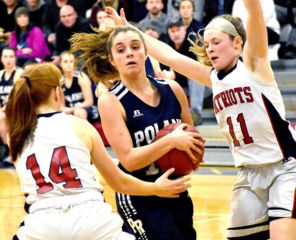 Poland's Nathalie Theriault drives between Eliza Hotham, left, and Alexa Thayer of Gray-New Gloucester during Thursday's game in Gray. Gray-New Gloucester won, 47-37,