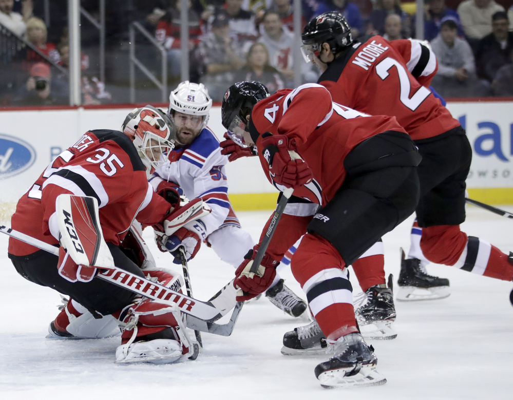 Devils goalie Cory Schneider and teammates Sami Vatanen, 45, and John Moore, 2, defend against Rangers center David Desharnais in the first period Thursday night in Newark, N.J.