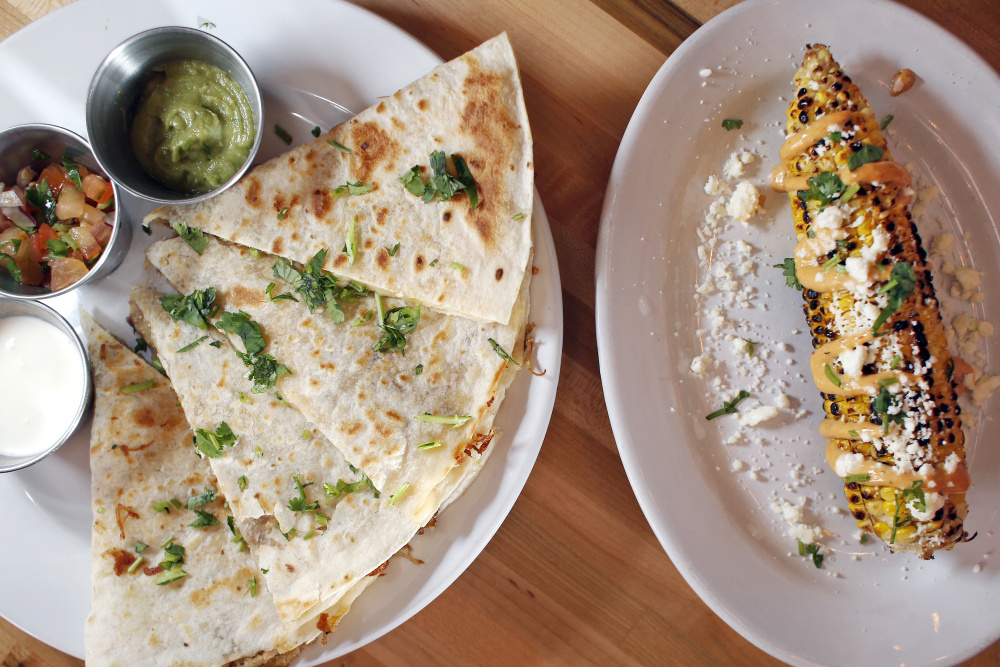 Carnitas quesadillas, left, with guacamole, Mexican crema and pico de gallo; and grilled Mexican-style corn on the cob with chipotle aioli, cotija cheese and cilantro.