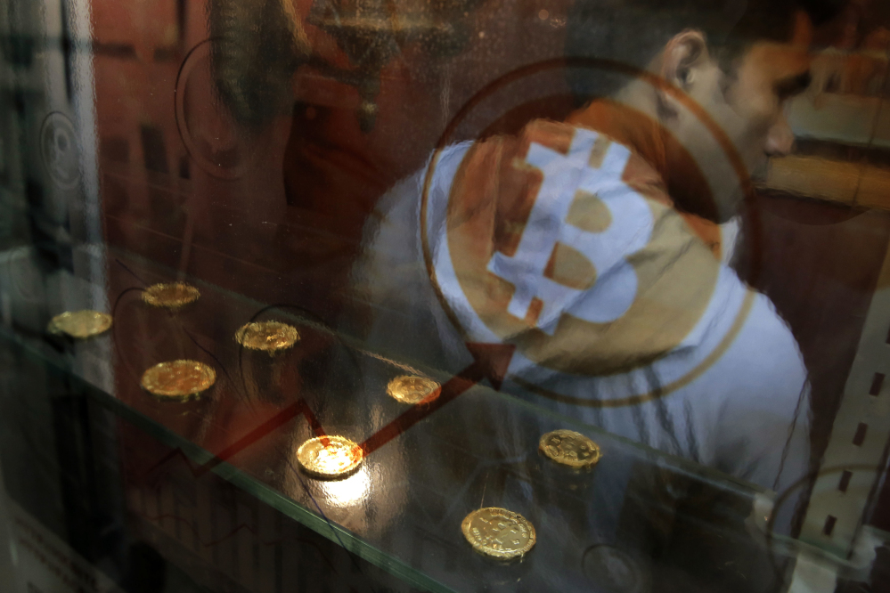 A man uses a Bitcoin ATM in Hong Kong. Bitcoin is the world's most popular virtual currency. The latest example of a company trying to tie its fortunes to the craze came Thursday in the form of an iced tea maker.