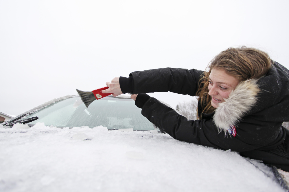 Madeline Paquette of Newton, Mass., reaches to clear ice from her windshield at the northbound Kennebunk rest area of the Maine Turnpike on Saturday morning.
