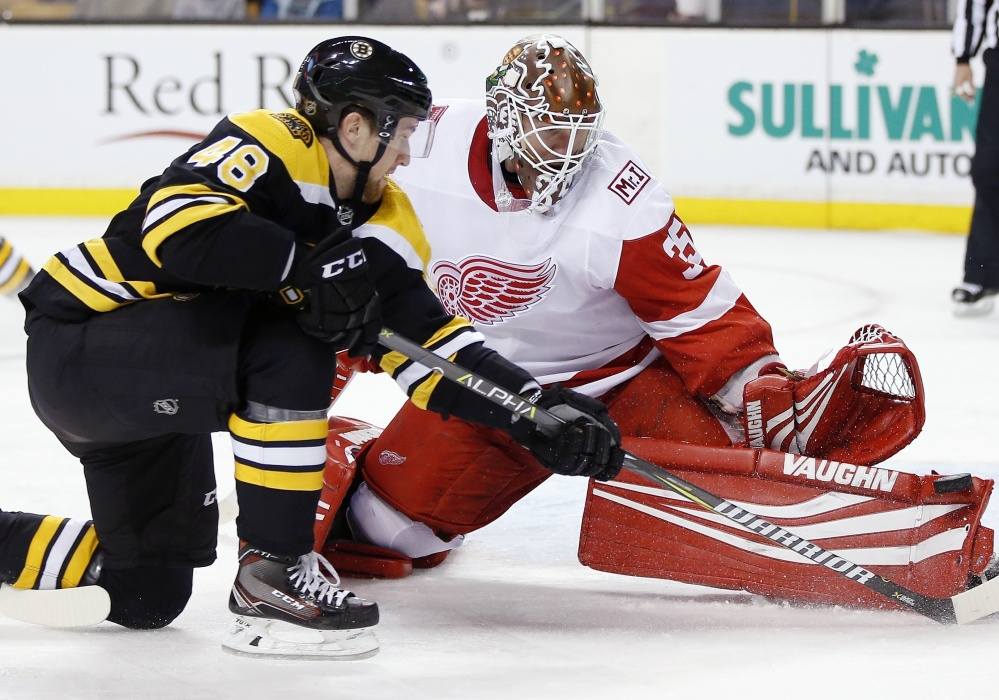 Detroit goalie Jimmy Howard, the former UMaine standout, blocks a shot by Boston's Matt Grzelcyk during the second period of Saturday's game in Boston. Howard made 23 saves, but the Bruins won, 3-1.