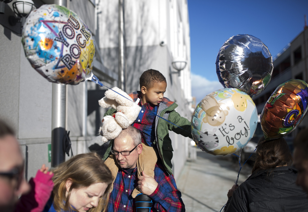 Rich Maynard, 40, holds Alden, 3, outside District Court in Portland. Rich and his wife, Napthali, below with Alden, became adoptive parents Wednesday. Alden, named for country singer Jason Aldean, is the latest addition to a family that includes two other foster kids.