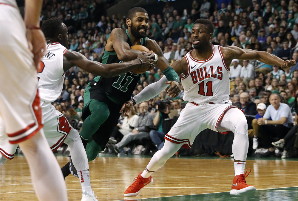 Kyrie Irving of the Celtics drives between Chicago's David Nwaba, right, and Jerian Grant during Saturday's game in Boston. Irving scored 25 points in a 117-92 victory.
