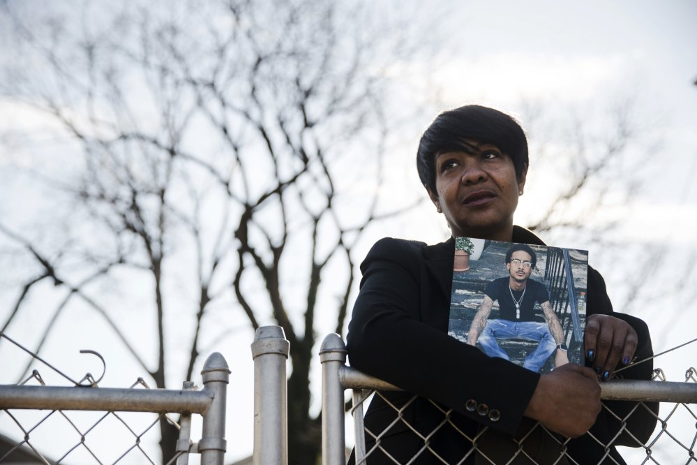 Trina Singleton poses Thursday in Collingdale, Pa., with a photograph of her eldest son, Darryl, who was murdered. Singleton says sharing Darryl's life story through The Philadelphia Obituary Project has helped the family move forward.