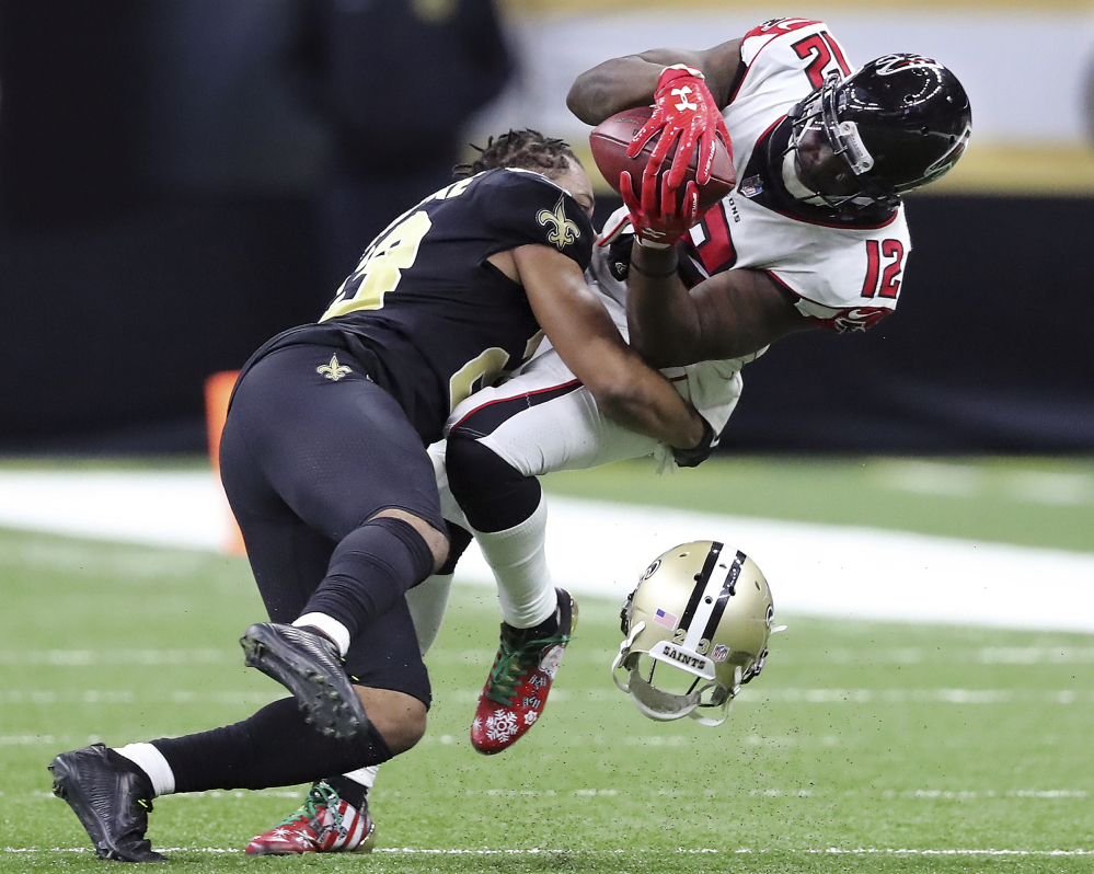 Cornerback Marshon Lattimore of the New Orleans Saints loses his helmet while bringing down Mohamed Sanu of the Atlanta Falcons following a reception Sunday during the third quarter of the Saints' 23-13 victory at home.