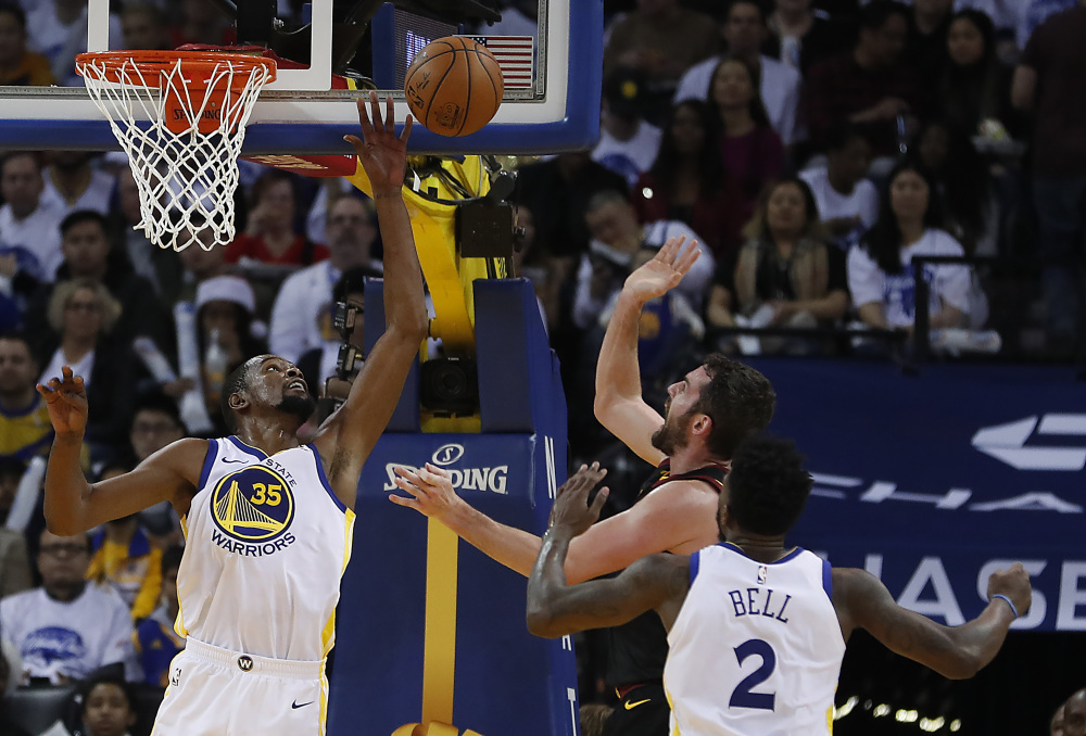 Golden State forward Kevin Durant blocks a shot by Cleveland forward Kevin Love during the second half in Oakland, Calif., on Monday. The Warriors won 99-92.