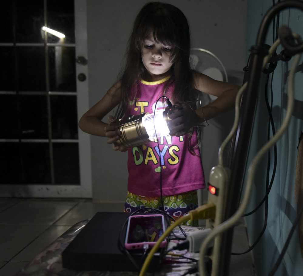 Melanie Oliveras Gonzalez, 6, holds a lantern Thursday in the living room of her house in Morovis, Puerto Rico. The U.S. Army Corps of Engineers has said it likely won't be until May that all of the island territory is electrified.