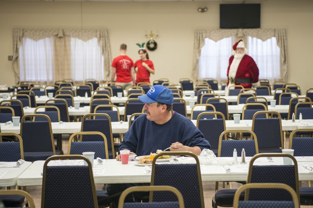 Michael Dawe sits at a table by himself Monday, Christmas Day, for the 11th annual Central Maine Family Christmas Dinner at the Elks Lodge in Waterville. If not for a major winter storm, all seats would have been occupied, judging by previous years' events.