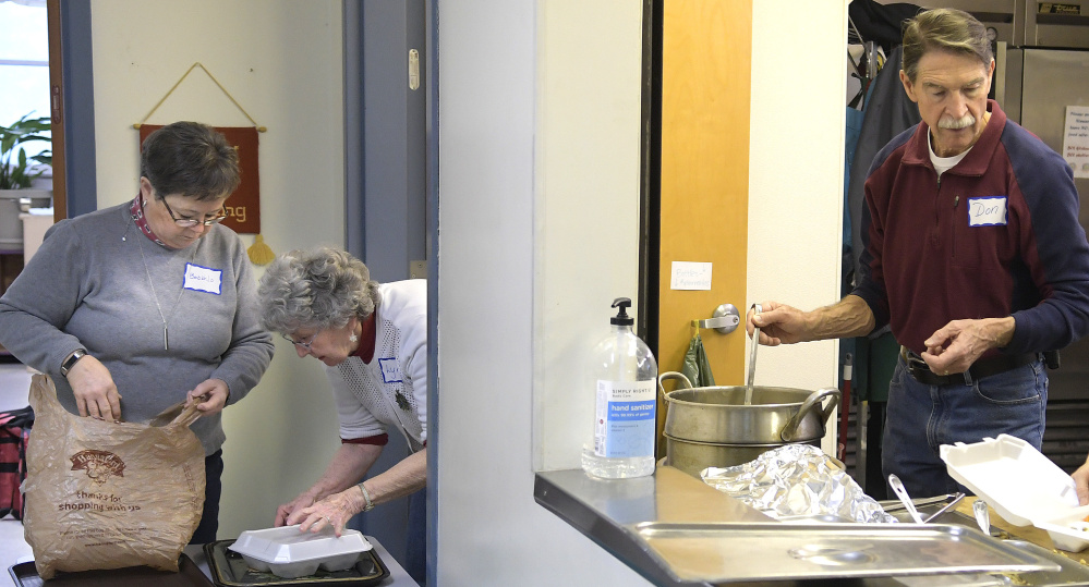 Volunteers prepare meals Monday at Emmanuel Lutheran Episcopal Church in Augusta. Over 250 meals were served by volunteers during whiteout conditions.