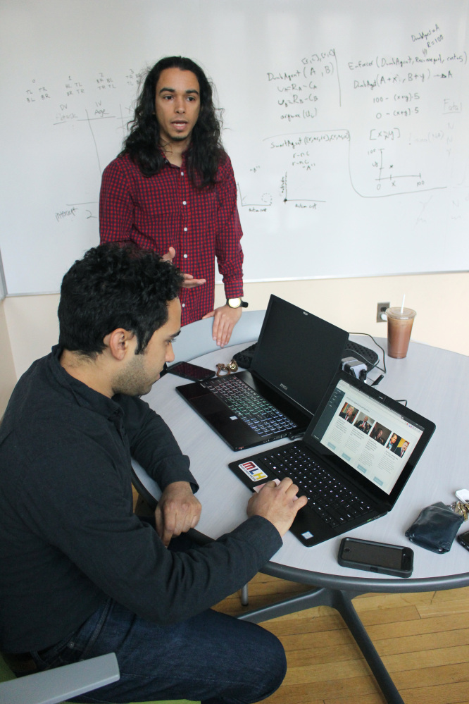 "In this Dec. 13, 2017, photo graduate students Michael Lopez-Brau, back, and Stefan Uddenberg show off the internet browser extension ""Open Mind,"" at Yale University in New Haven, Conn. The pair helped create the extension with students from Cal Tech and Waterloo University. The extension is designed to flag fake and biased news stories and provide the reader with alternatives. (AP Photo/Pat Eaton-Robb)"