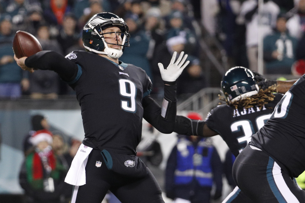 Philadelphia quarterback Nick Foles passes against the Oakland Raiders on Monday night in Philadelphia. The Eagles won, to clinch the top seed in the NFC.