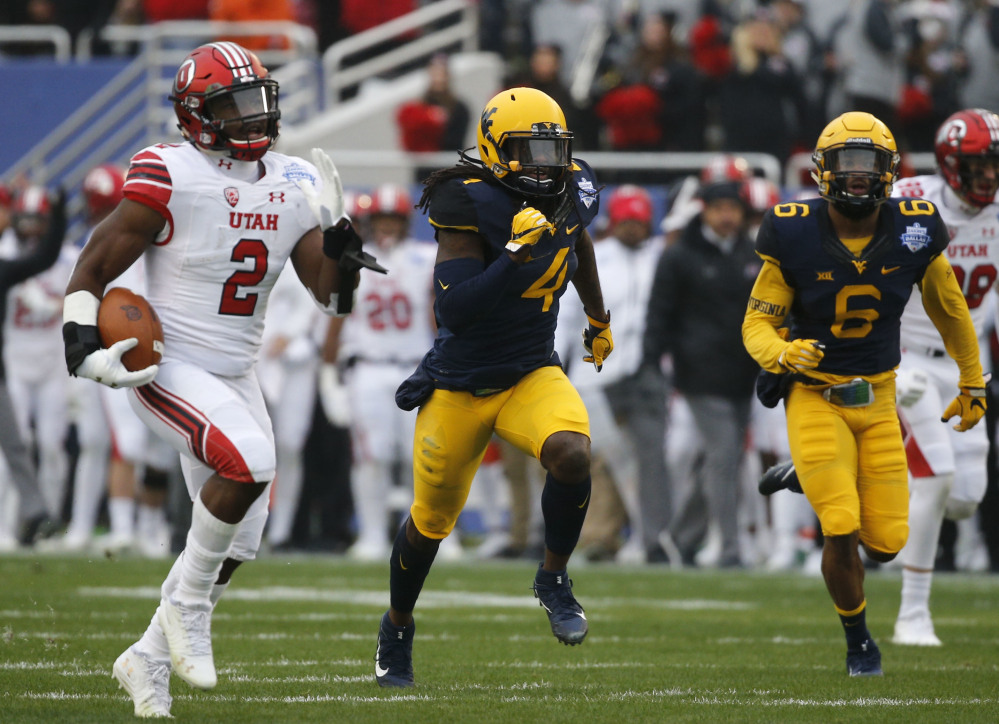 Zack Moss of Utah outruns the West Virginia secondary to the end zone to score Tuesday during the first half of Utah's 30-14 victory in the Heart of Dallas Bowl.