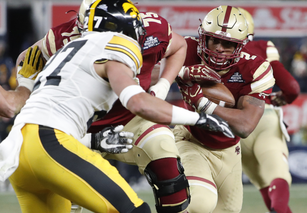 Iowa safety Amani Hooker, left, looks to tackle Boston College running back AJ Dillon on a 39-yard catch and run during the Pinstripe Bowl Wednesday in New York, where the kickoff temperature was 23 degrees.