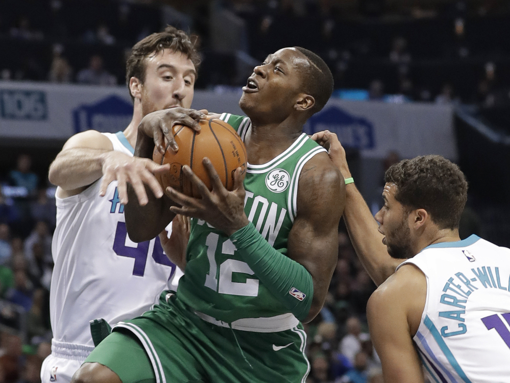 Boston's Terry Rozier is fouled as he drives between Charlotte's Frank Kaminsky, 44, and Michael Carter-Williams in the first half Wednesday night in Charlotte, N.C.