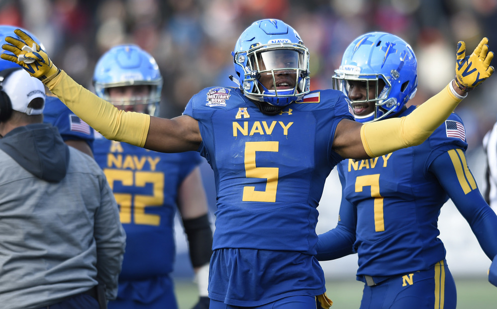 Navy's Justin Norton celebrates holding a fourth-down stop against Virginia in the first half of the Midshipmen's 49-7 rout in Military Bowl on Thursday in Annapolis, Md.