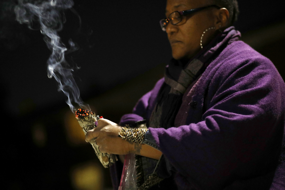 Erricka Bridgeford burns sage as she performs a ceremony near the scene of a homicide in Baltimore. Bridgeford lost a brother, a stepson, and three cousins to gun violence.
