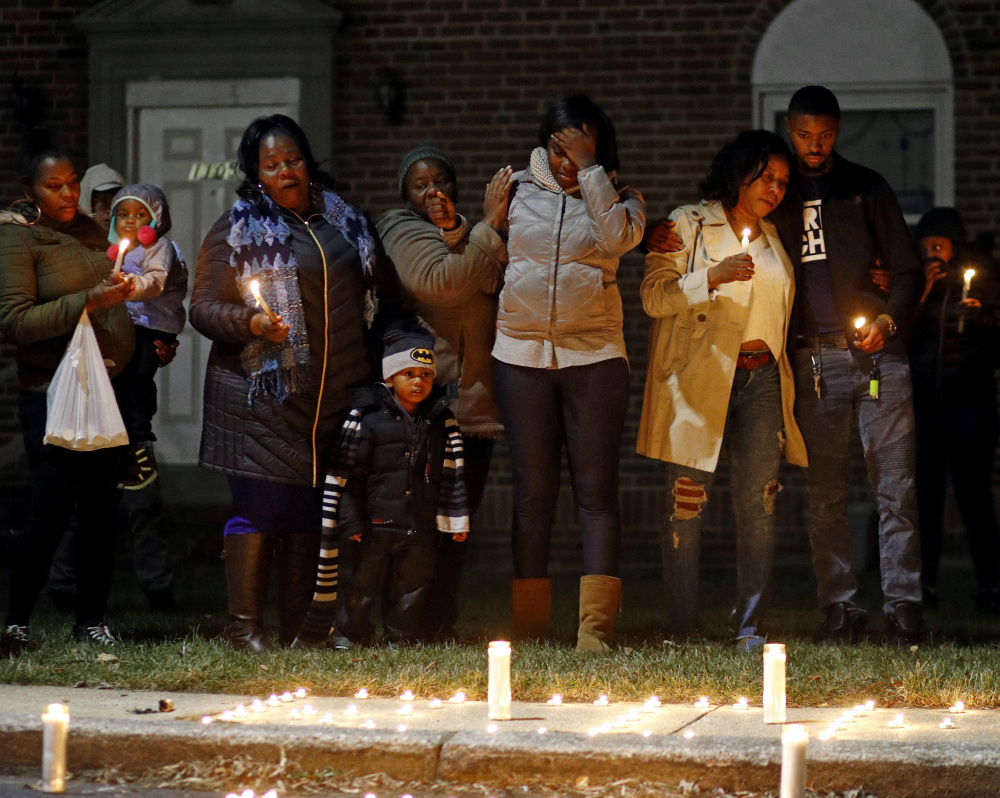 Relatives of a homicide victim gather for a vigil near the scene of the murder in Baltimore, Md., where friends and family of the victim joined activist Erricka Bridgeford.