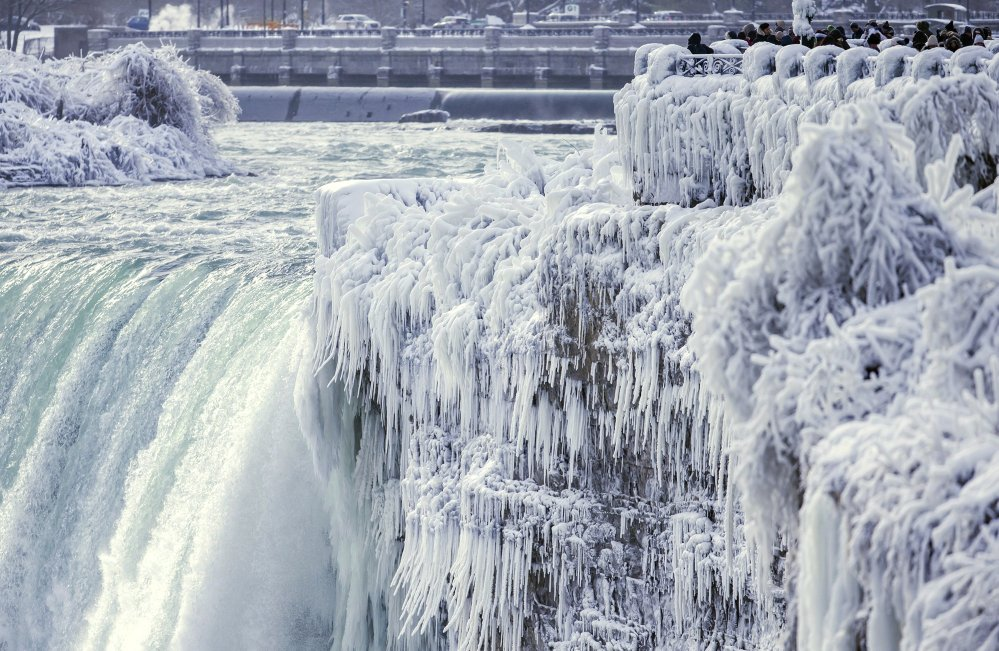 Visitors take photographs at the brink of the Horseshoe Falls in Niagara Falls, Ontario, as cold weather continued through much of the province Friday.