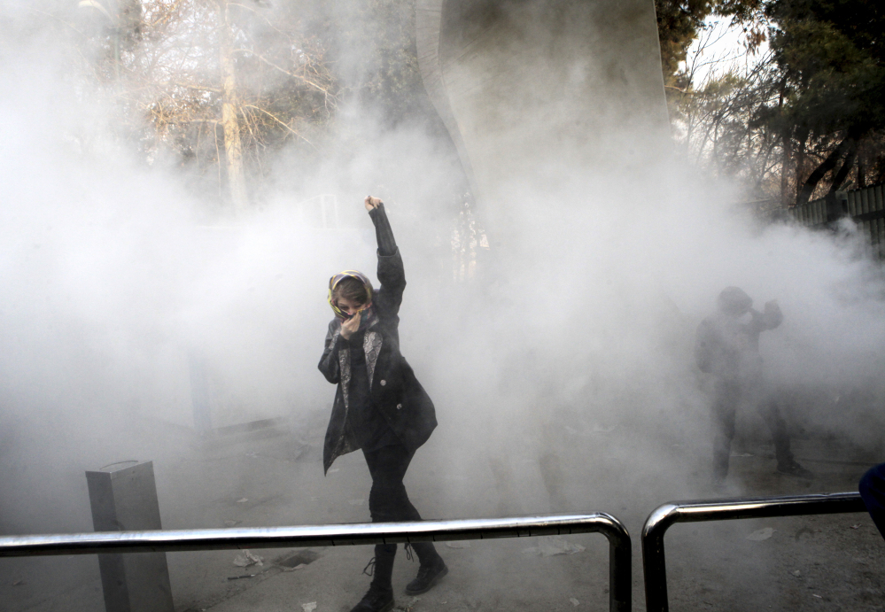 A university student attends a protest inside Tehran University while a smoke grenade is thrown by anti-riot police in Tehran, Iran, on Saturday. A wave of spontaneous protests over Iran's weak economy swept Tehran on Saturday, with college students and others chanting against the government just hours after hard-liners held their own rally.