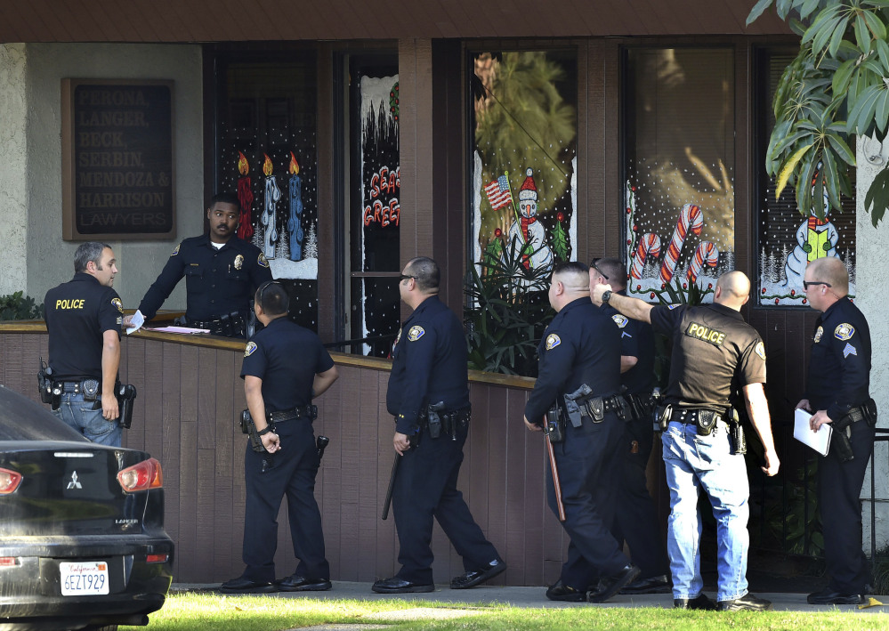 Police gather in front of law offices where a deadly shooting took place in Long Beach, Calif., Friday.