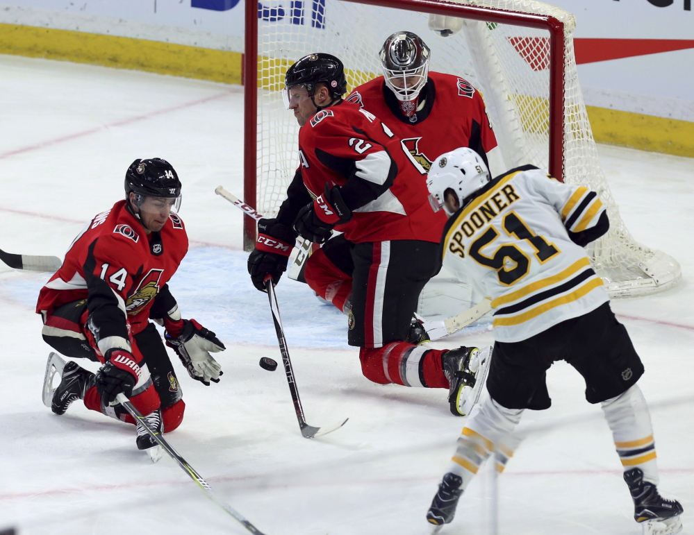 Boston Bruins' Ryan Spooner shoots the puck and scores as Senators' Alexandre Burrows (14) and Dion Phaneuf (2) defend during the first period Saturday in Ottawa, Ontario.
