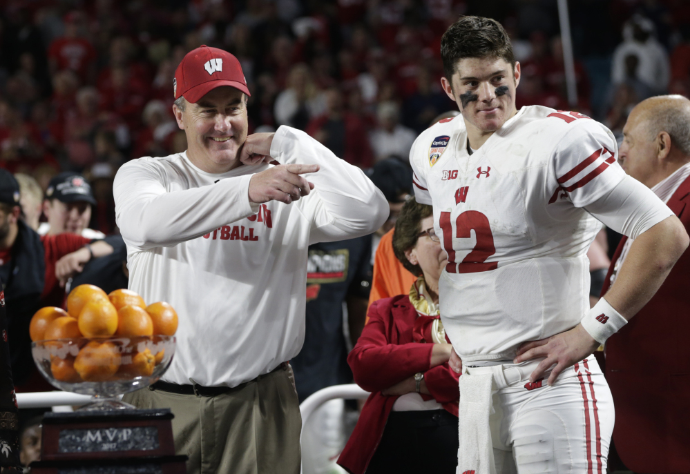 Wisconsin coach Paul Chryst and quarterback Alex Hornibrook stand next to the MVP trophy at the end of the Orange Bowl game against Miami on Saturday night in Miami Gardens, Fla. Hornibrook won the MVP trophy and Wisconsin defeated Miami 34-24.