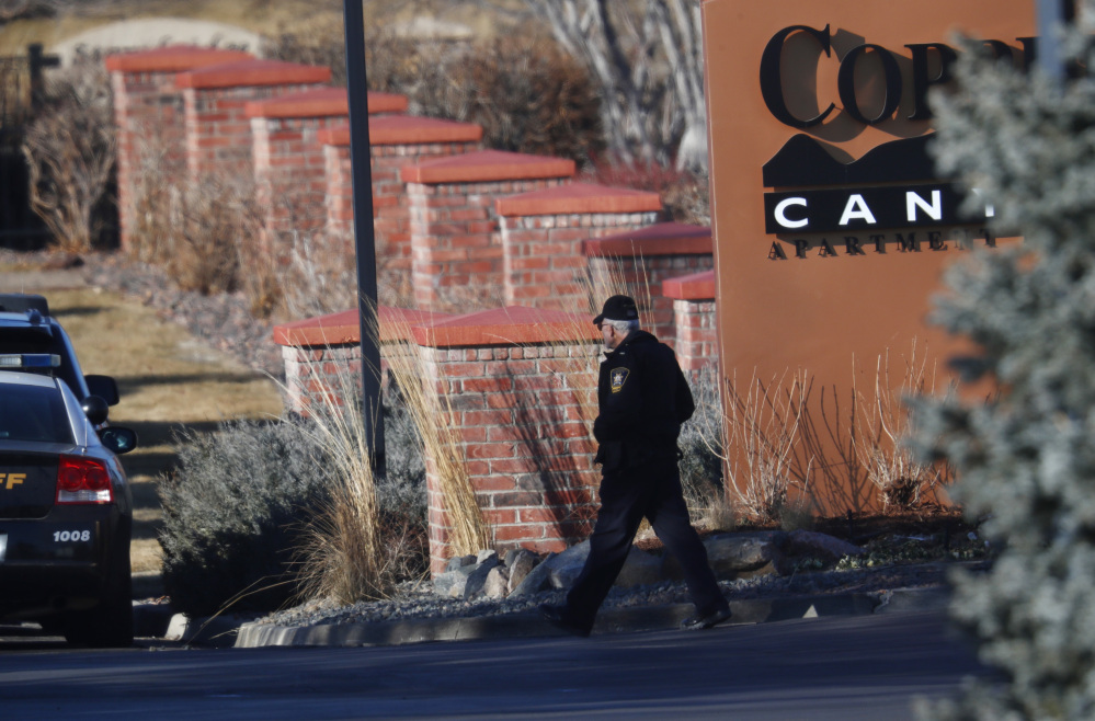 An investigator heads to the scene of a shooting Sunday in Highlands Ranch, Colo.