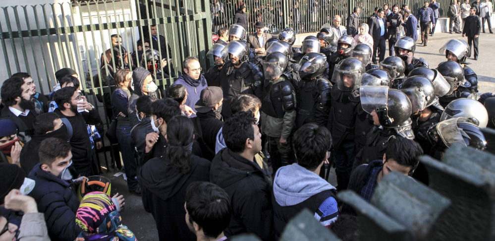 In photo taken by an individual not employed by the Associated Press and obtained outside Iran, anti-riot police prevent university students from joining others protesting Iran's weak economy in Tehran on Saturday. The outpouring of public discontent is the most widespread since 2009.