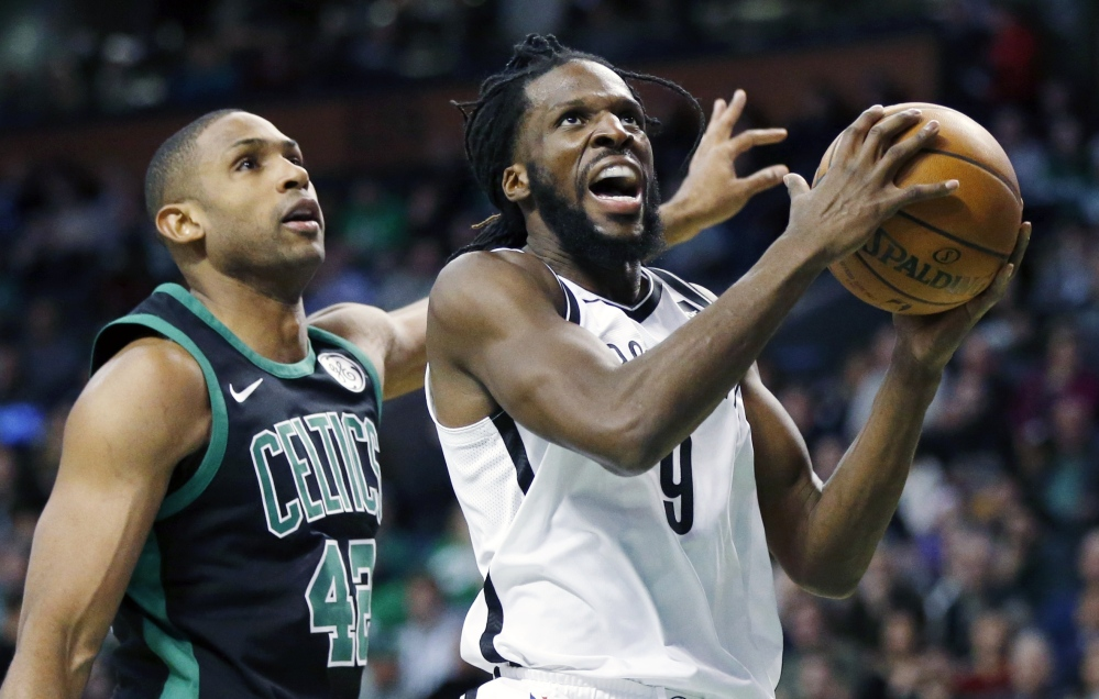 Brooklyn's DeMarre Carroll goes up to shoot in front of Boston's Al Horford during the Celtics' 108-105 win Sunday in Boston.