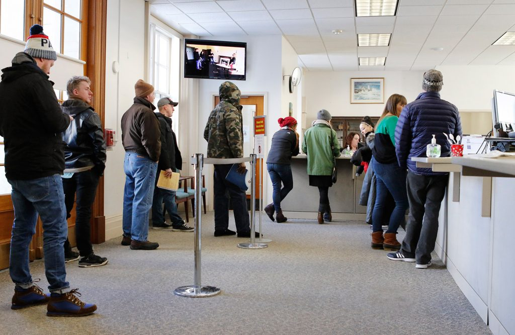 Residents wait in line Thursday at Portland City Hall to pay property tax bills or register vehicles. But many municipalities, including Portland, are not accepting prepayments for taxes that have yet to be assessed on properties.