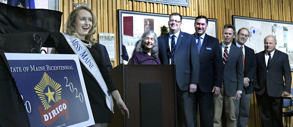 Miss Maine, Katie Elliott, unveils the Maine Bicentennial Commemorative License Plate on Monday in Augusta.