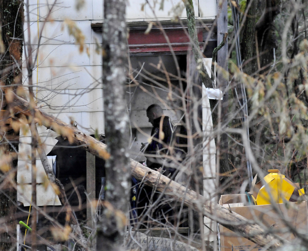An investigator with the Maine State Police is seen inside a run-down home off Route 150 in Skowhegan on Wednesday. Police searched the building and a nearby mobile home on Tuesday for any clues to the disappearance of Tina Stadig, who has been missing for nearly six months.