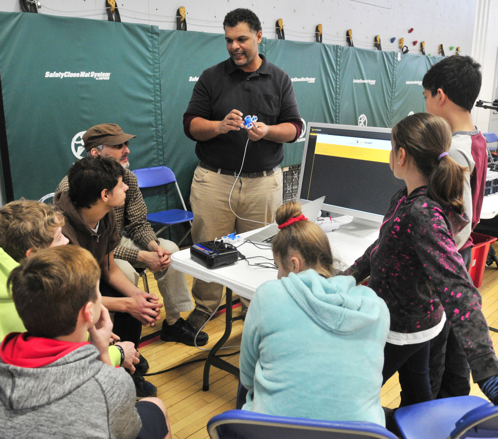 Kristopher Kleva holds a small drone as he talks about how to program the guidance system on the computer during a demonstration for Augusta Boys and Girls Club on Friday at The Buker Center in Augusta.