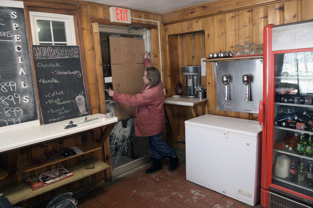 The Hi-Hat Pancake House manager Mary Laflin replaces cardboard on a door that was shattered early Tuesday when the Farmingdale restaurant was broken into. An ATM machine was stolen.