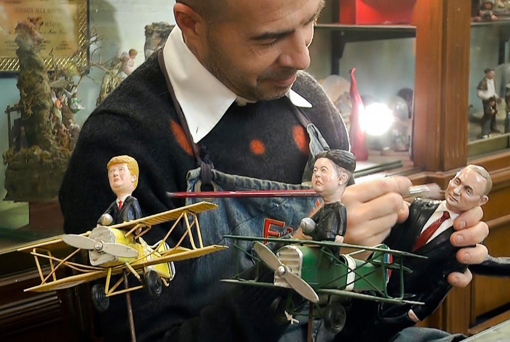 Artisan Marco Ferrigno puts finishing touches to statuettes of U.S. President Trump, Russian leader Vladimir Putin and North Korean leader Kim Jong Un in his shop in Naples, Italy, on Wednesday. Naples' Christmas artisans are turning figures from current events into ceramic characters to decorate miniature Nativity scenes.