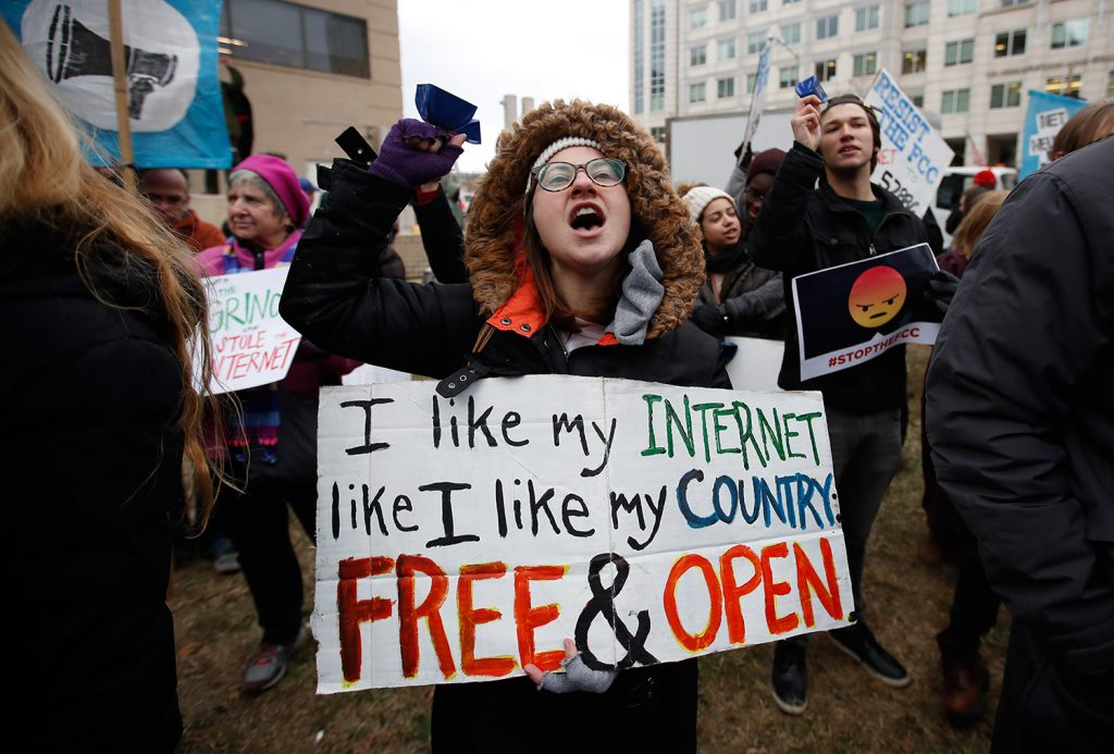"Lindsay Chestnut of Baltimore holds a sign that reads ""I like My Internet Like I Like my Country Free & Open"" as she protests near the Federal Communications Commission Thursday in Washington."