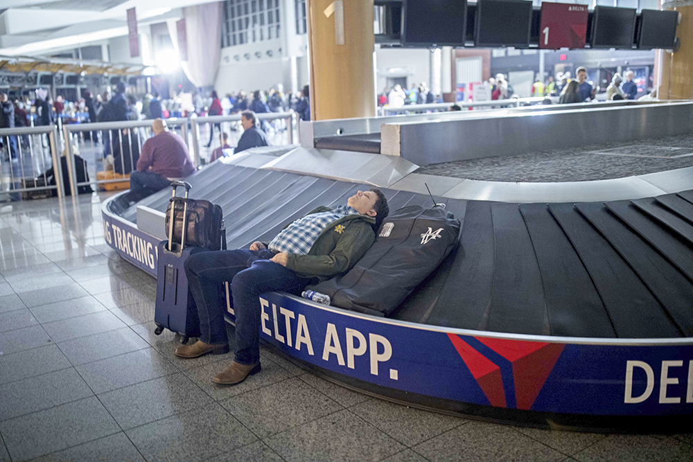 A traveler sleeps on a baggage carousel at Hartfield-Jackson Atlanta International Airport, Sunday after a power outage grounded scores of flights and during one of the busiest travel times of the year.