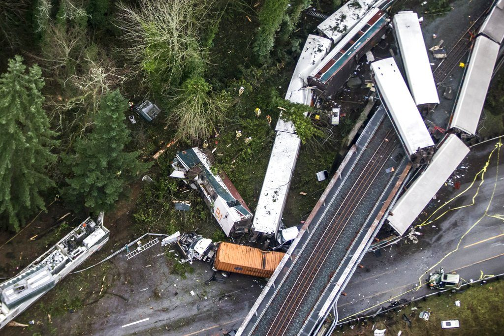 Train cars lie where they spilled onto Interstate 5 Monday,  in DuPont, Wash. The Amtrak train was making its first-ever run along a faster new route when it hurtled off the overpass.