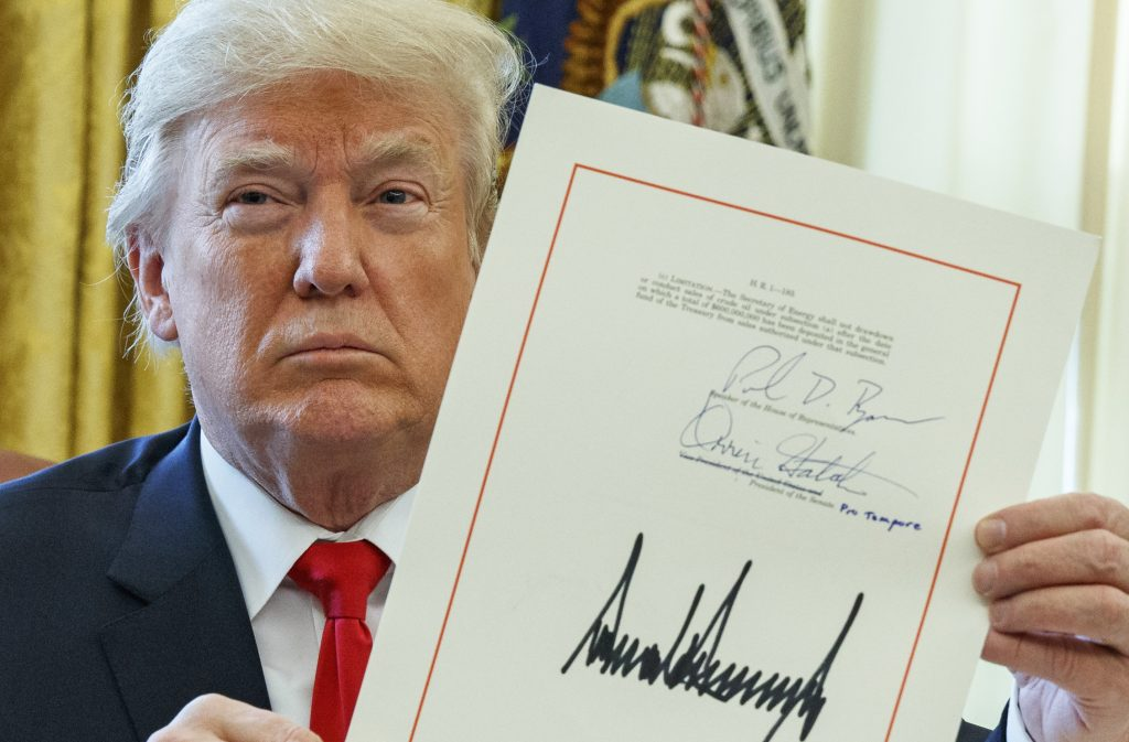President Trump shows off the tax bill after signing it in the Oval Office on Friday.