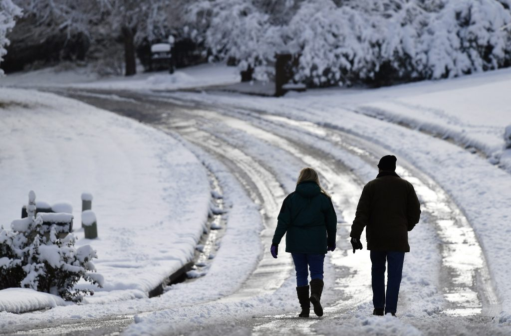 People walk down a snow-covered road after a heavy snow Saturday in Kennesaw, Georgia. The frigid temperatures behind a cold front combined with moisture off the Gulf of Mexico to bring unusual wintry weather to parts of the South.