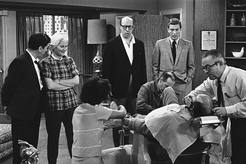 Rose Marie stands to the left of Morey Amsterdam, with Richard Deacon, and Dick Van Dyke, right, as cast members gather around Carl Reiner, in barber chair during a rehearsal of an episode for the