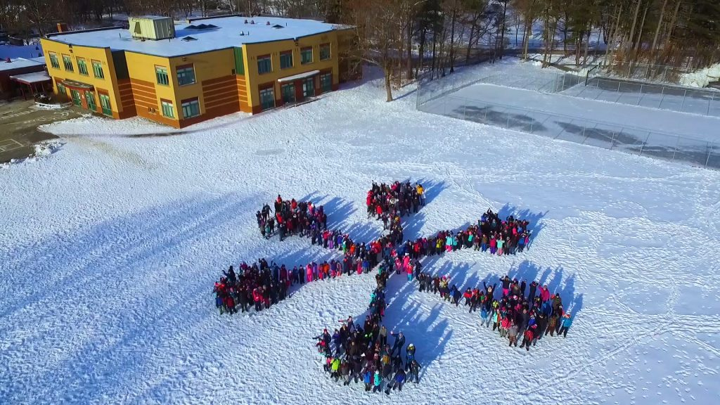 Students and staff members at Skillin Elementary School in South Portland gathered in the schoolyard Friday, forming a 430-person snowflake that was photographed from above by a drone to promote the upcoming 2018 Winter Games in January coordinated by the nonprofit WinterKids organization. Skillin is one of 16 schools across Maine selected to participate in the outdoor activity and nutrition challenge.