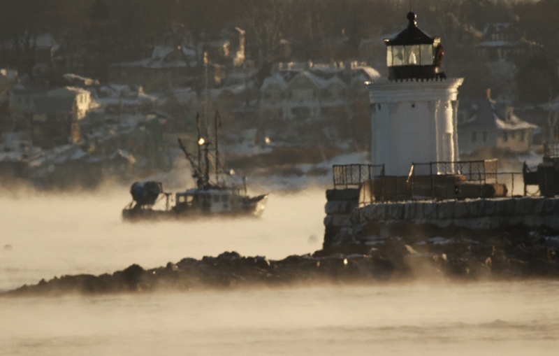 A fishing vessel motors through sea smoke, past Bug Light on Wednesday morning.