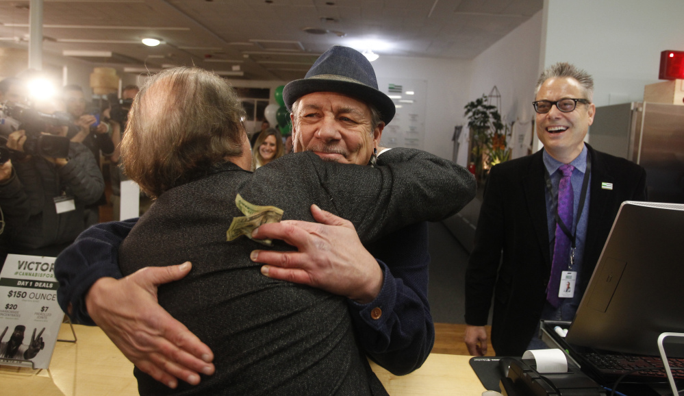Steve DeAngelo, CEO, center, and brother Andrew DeAngelo, chief revenue officer, make the first sale of recreational marijuana to Henry Wykowski at Harborside marijuana dispensary in Oakland, Calif. As of Monday, recreational marijuana can be sold legally in California.