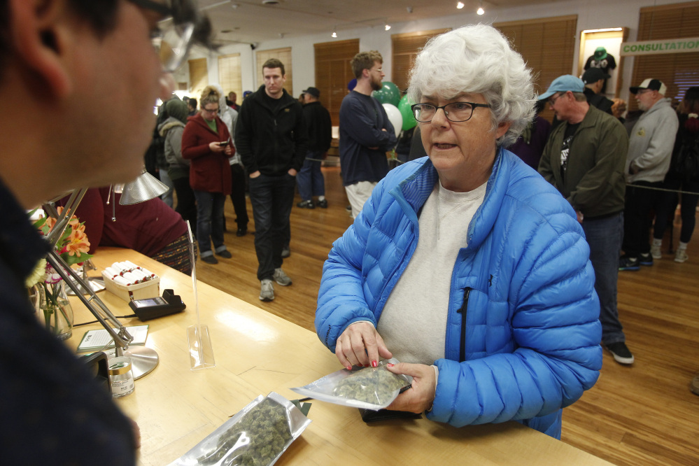 Margot Simpson purchases marijuana at Harborside marijuana dispensary Monday in Oakland, Calif. The dispensary offered early customers joints for a penny.