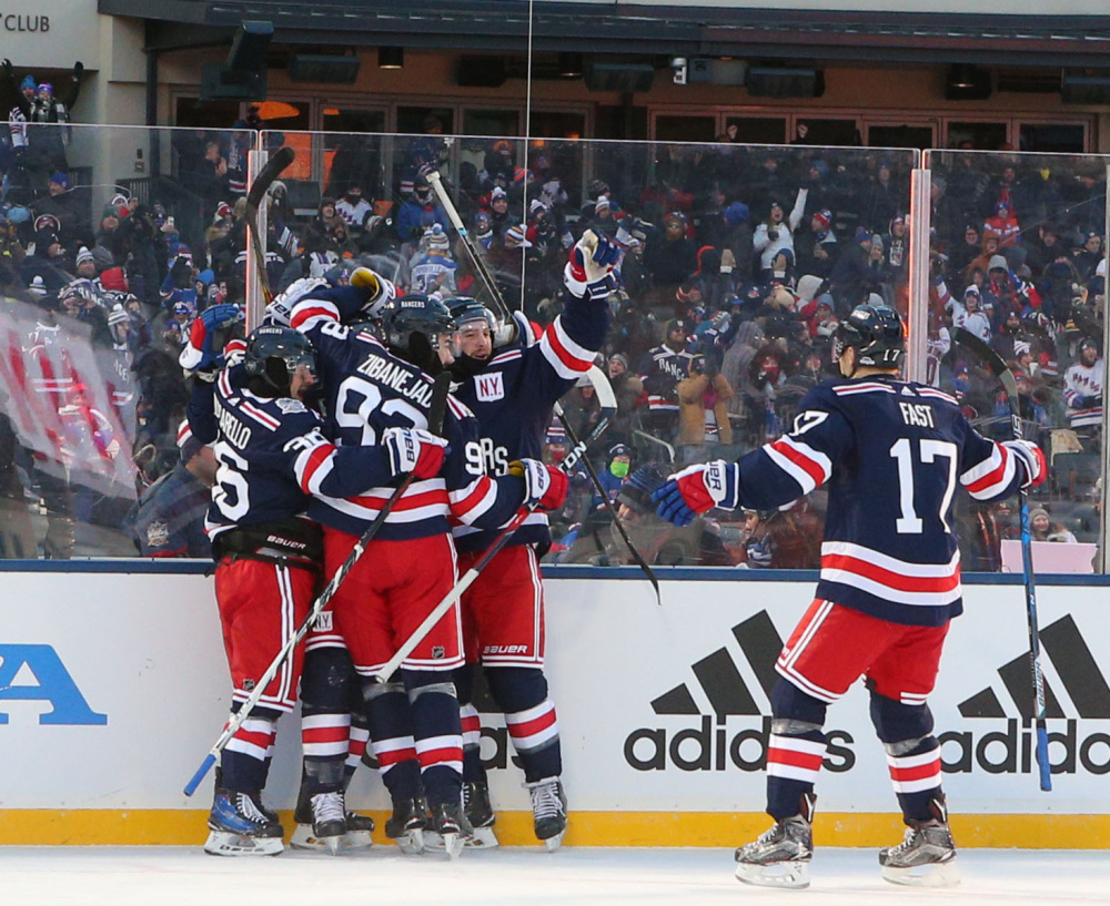 New York Rangers players celebrate Monday afternoon after an overtime goal by J.T. Miller ended the NHL Winter Classic, giving the Rangers a 3-2 win over the Buffalo Sabres.